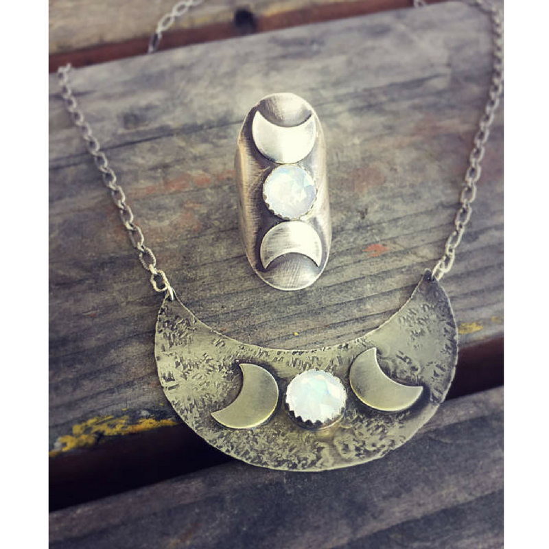 Triple Moon Goddess Ring with a Moonstone Moon phases photographed on a flat surface with matching necklace