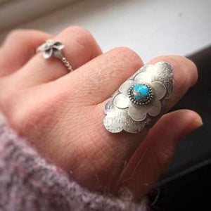 Turquoise Flower Statement Ring photographed on a finger, in which The stone is set on a simple flower design and centered in a circle of silver beads