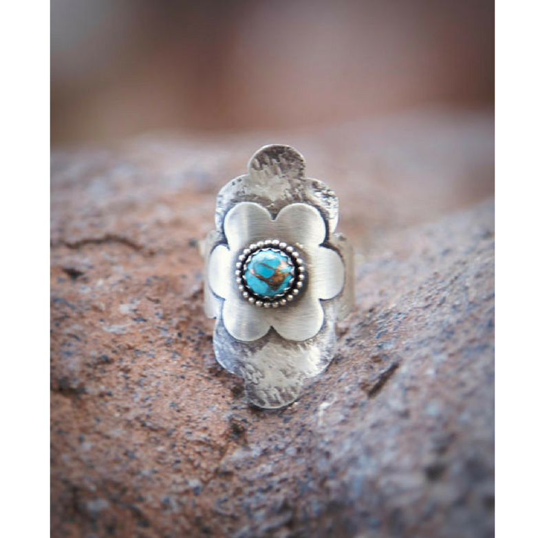 Turquoise Flower Statement Ring front view sitting between rocks