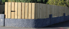 board and batten fence sitting on retaining wall