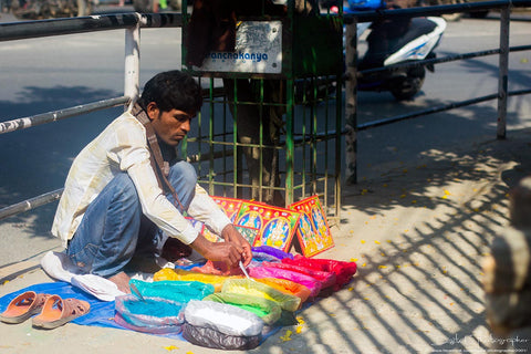 A man selling color powder on busy footpath at Jawalakhel, Lalitpur, Nepal