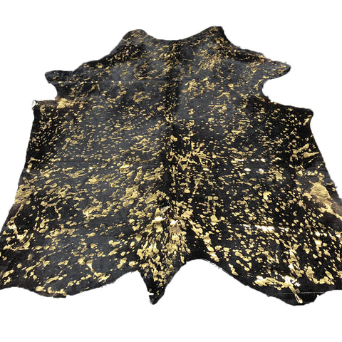 Metallic gold over black hair on cowhide