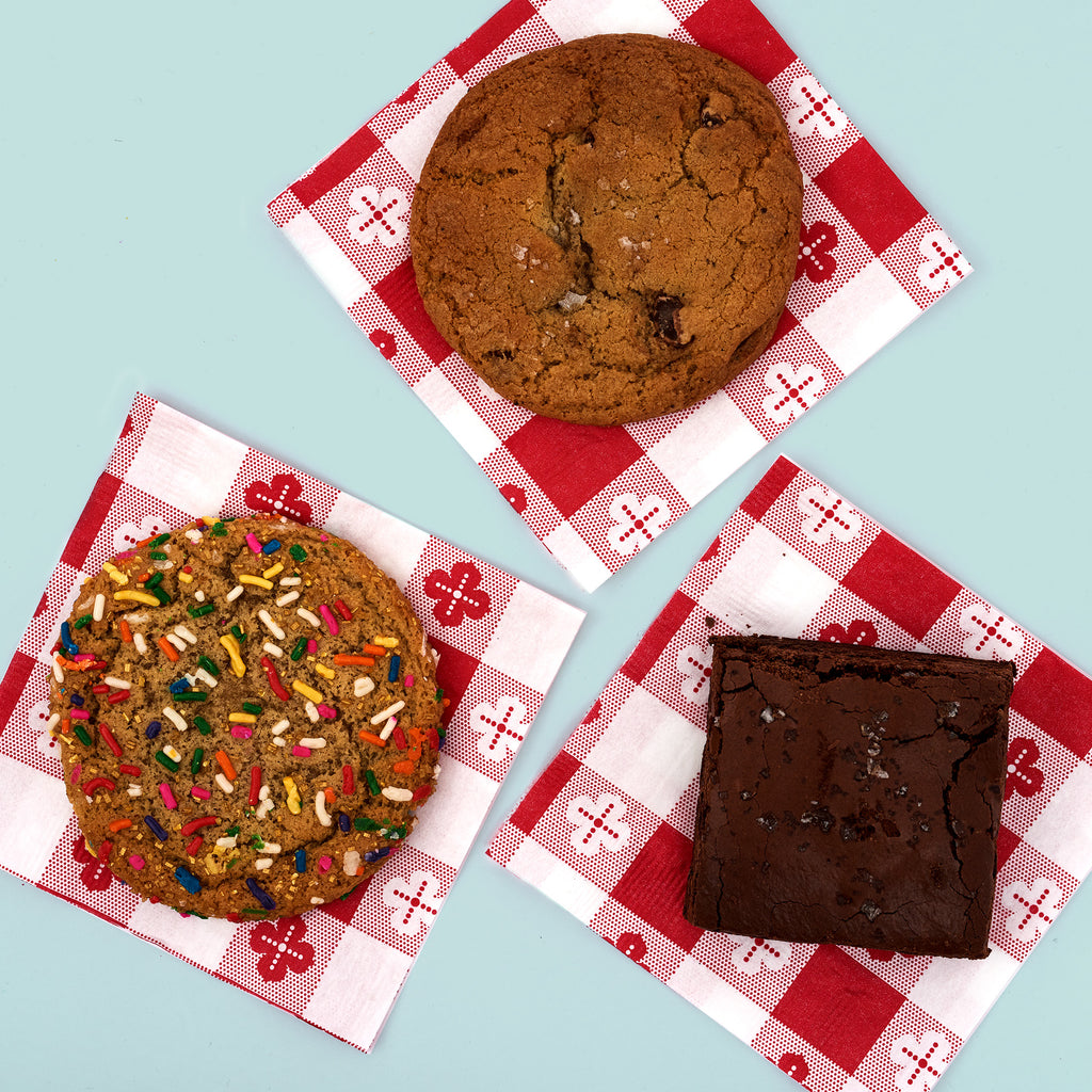1 Salted Chocolate Chip Cookie, 1 Unicorn Treat, and 1 Triple Chocolate Brownie each on a red gingham napkin.