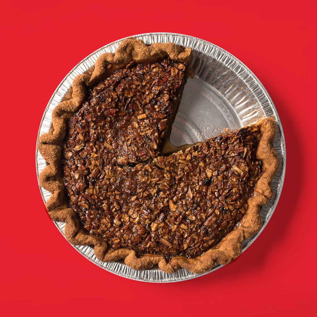 9in Bourbon Ginger Pecan pie on a red background with one slice removed