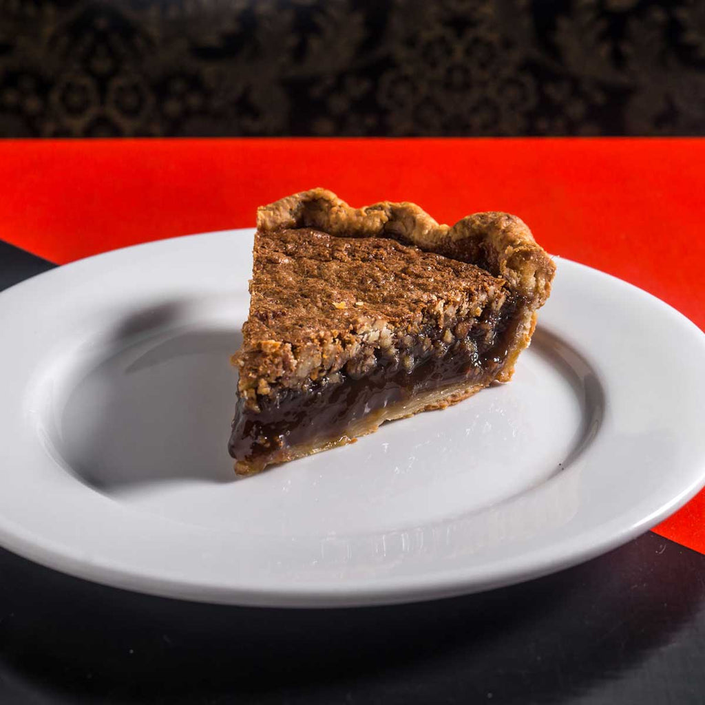 slice of bourbon ginger pecan pie on a white plate