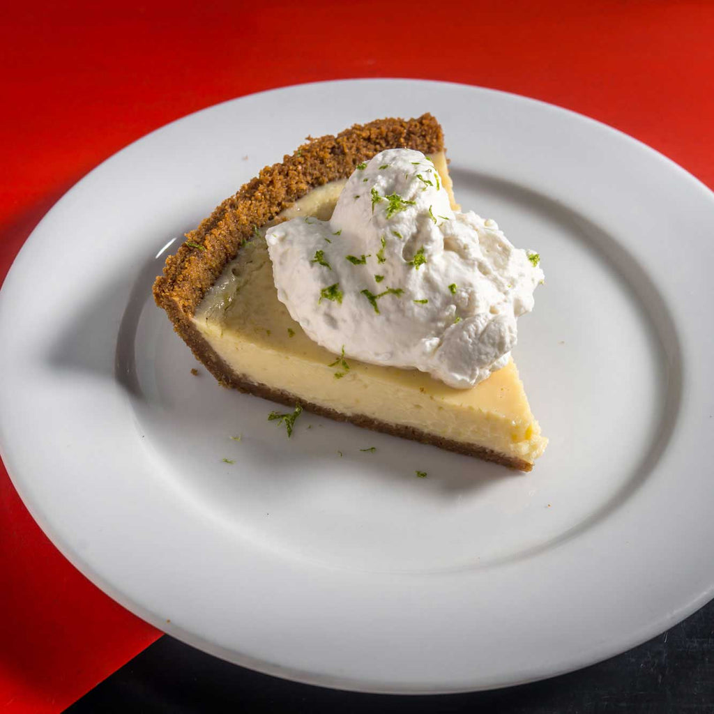 One slice of Butter & Scotch Key Lime pie with whipped cream and lime zest on top