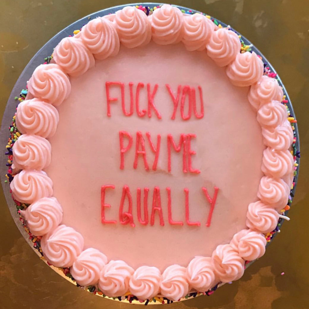 "Pink Butter & Scotch Birthday Cake that says ""Fuck You Pay Me Equally"" in hot pink writing"