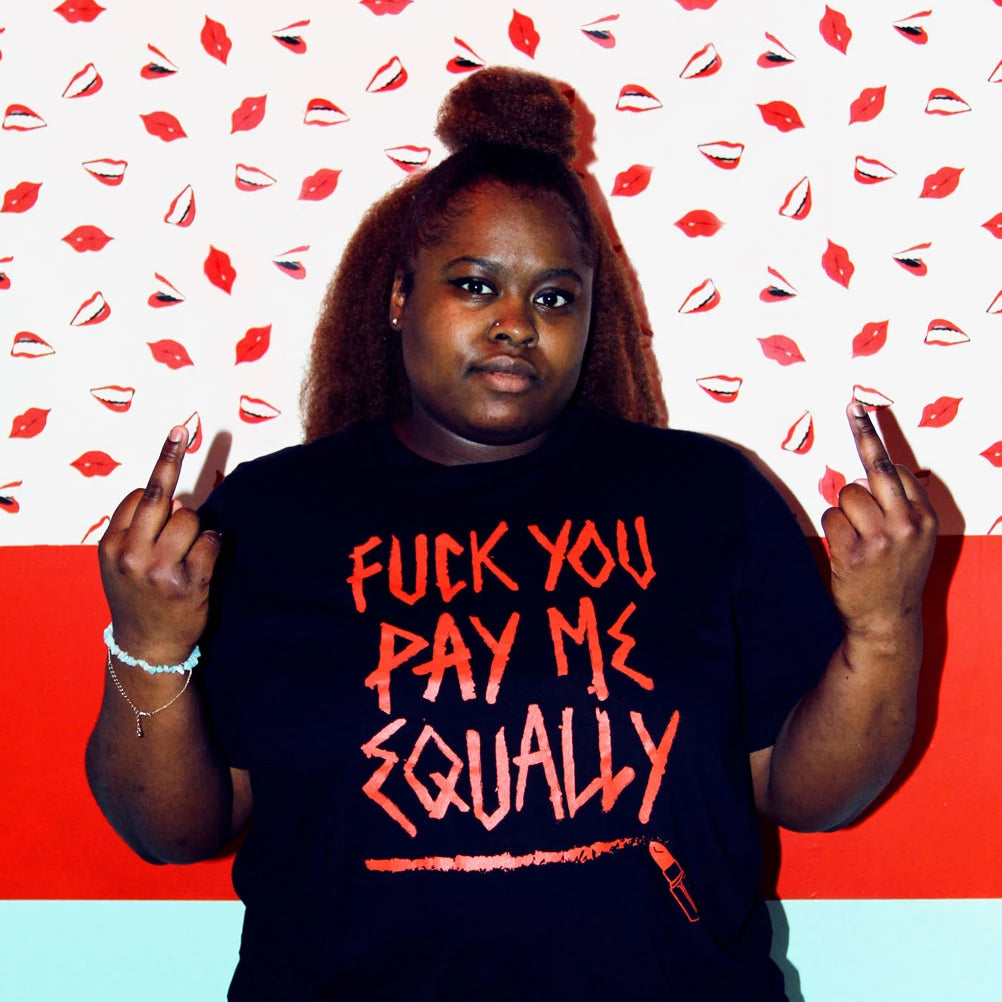 "Jenny wears a size large black short sleeve t-shirt that says ""Fuck You Pay Me Equally"" on it in red letters that look like they've been drawn with red lipstick"