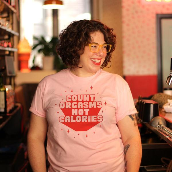 Allison Kave wears a size large pink short sleeve t-shirt that says Count Orgasms Not Calories in red type with sparkles around it