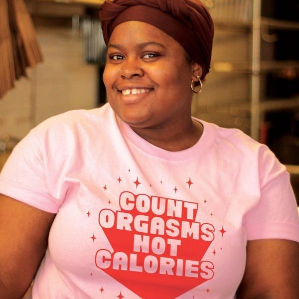 Jenny Louis wears a size large pink short sleeve t-shirt that says Count Orgasms Not Calories in red type with sparkles around it