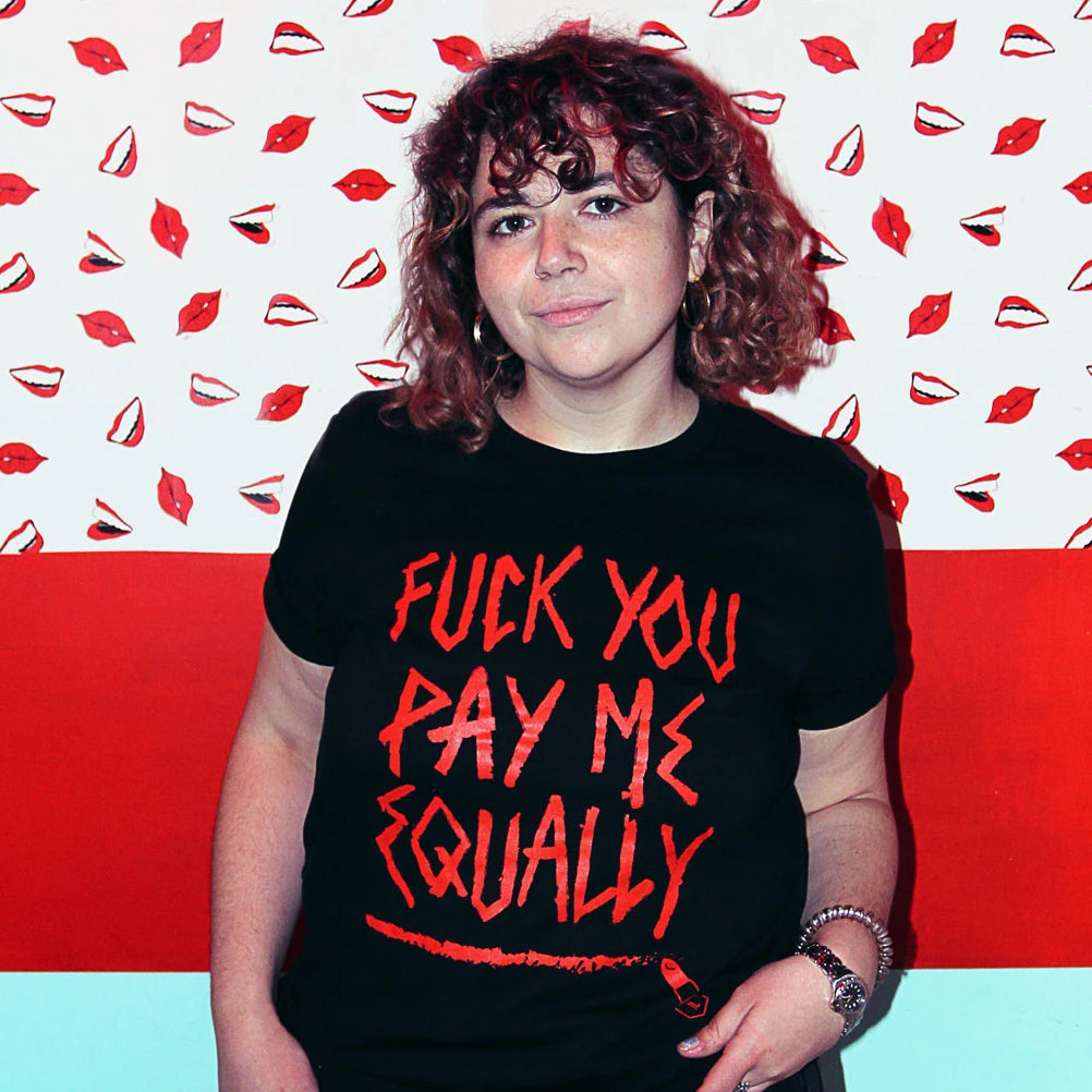 "Sam wears a size medium black short sleeve t-shirt that says ""Fuck You Pay Me Equally"" on it in red letters that look like they've been drawn with red lipstick"