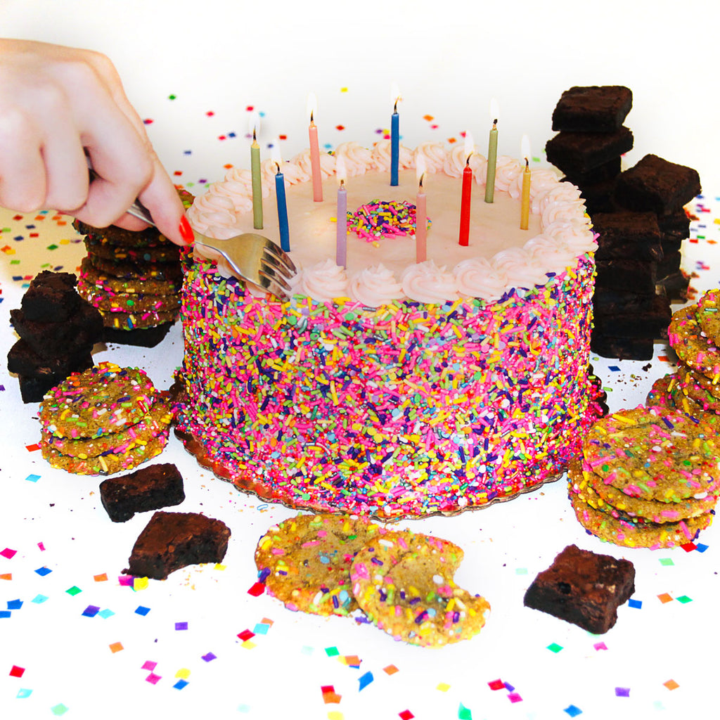hand with red nails holding a fork that is taking a bite from a pink Butter & Scotch Birthday Cake with unicorn treats and mini chocolate brownies around it. On a white background with rainbow confetti