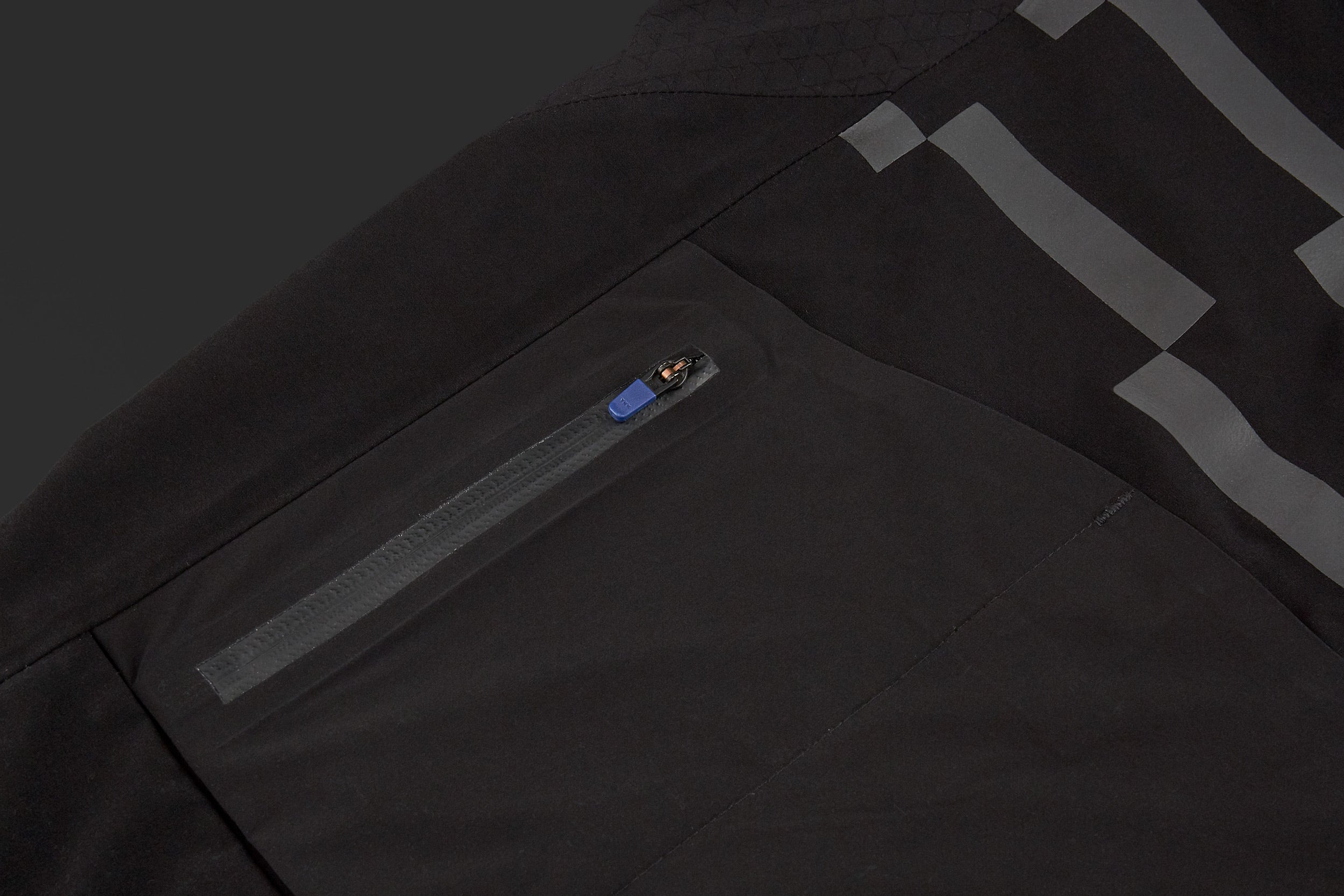 The dropped tail and elasticated hem has an embossed silicon gripper, designed to keep the garment in place and your jersey and rear pockets covered, even when riding hard out of the saddle. A concealed pocket for stowing the garment's Control Unit is highlighted with a colour-matched red zip.