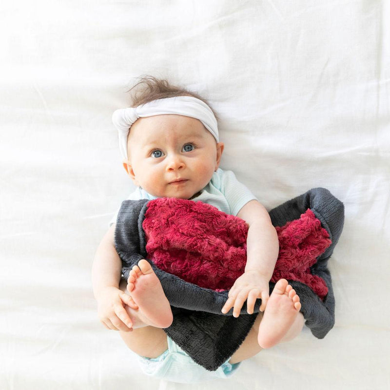 Infant girl holds a soft lovey blanket with rich red swirls and a charcoal lush back.