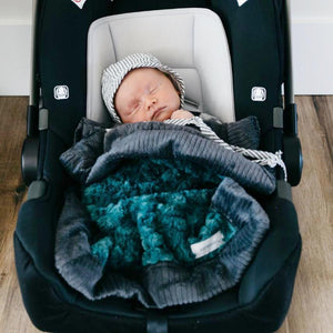 Newborn naps in a car seat while covered in an emerald baby security blanket.