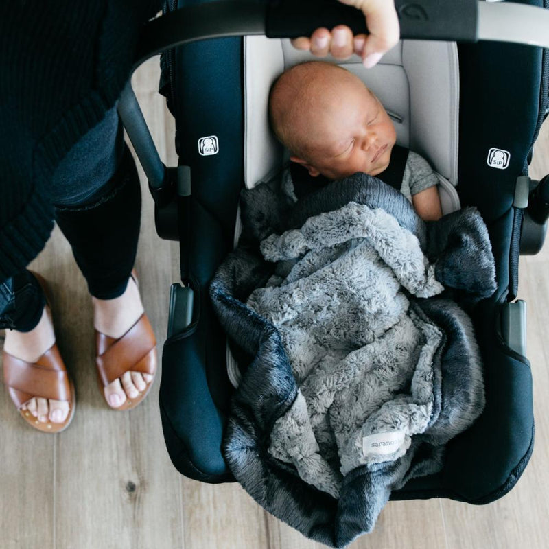 Mom carries newborn in car seat with a gray Saranoni infant baby blanket.