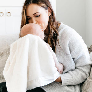Mom cuddling baby in an all Ivory baby blanket made my newborns.