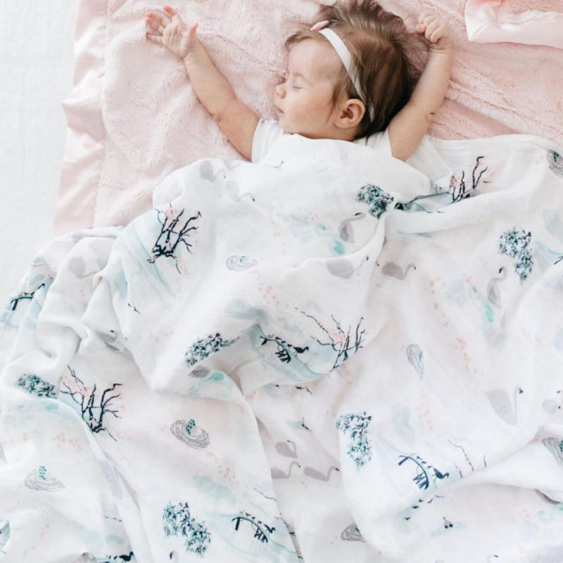 Baby wrapped in a summer swaddle blanket with flowers swans, and ducklings. Perfect baby sleep swaddle.