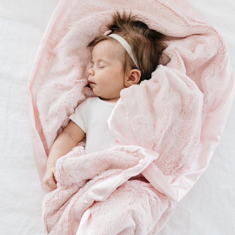 Cute baby girl takes a nap with her favorite pink security lush blanket.