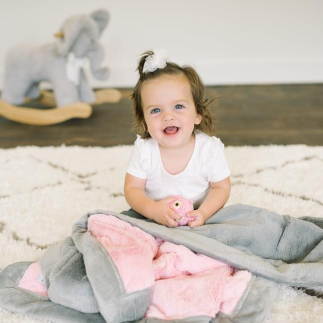 Little girl sits with her pink and gray receiving blanket