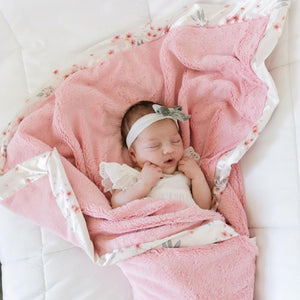 Newborn wrapped in cozy pink satin floral baby blanket.