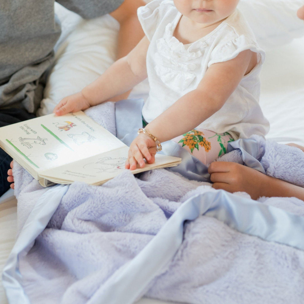 Little girl sits and reads book with lavender satin blanket