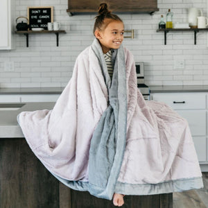 Little girl hanging out in the kitchen wrapped up in a beautiful lilac oversized throw blanket.