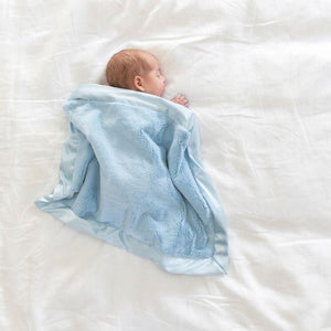 Baby boy cuddled underneath a light blue baby blanket with luxurious satin border.