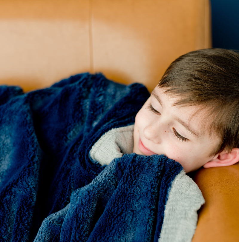 Young boy clutches his twin blanket featuring beautiful deep navy and light gray tones.