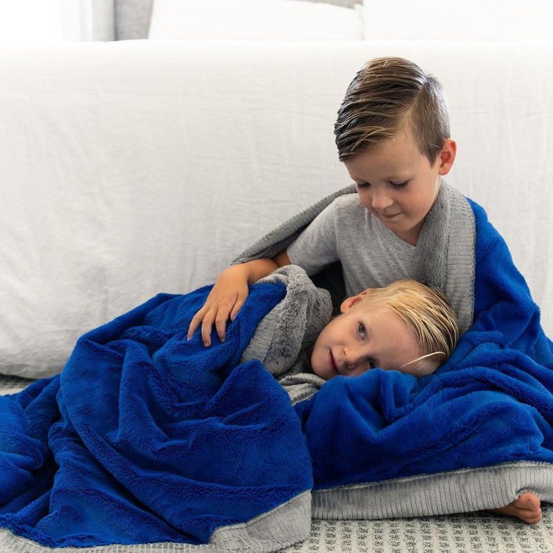 Young boy resting on his brother while being wrapped in a big Royal Blue and Gray throw blanket.
