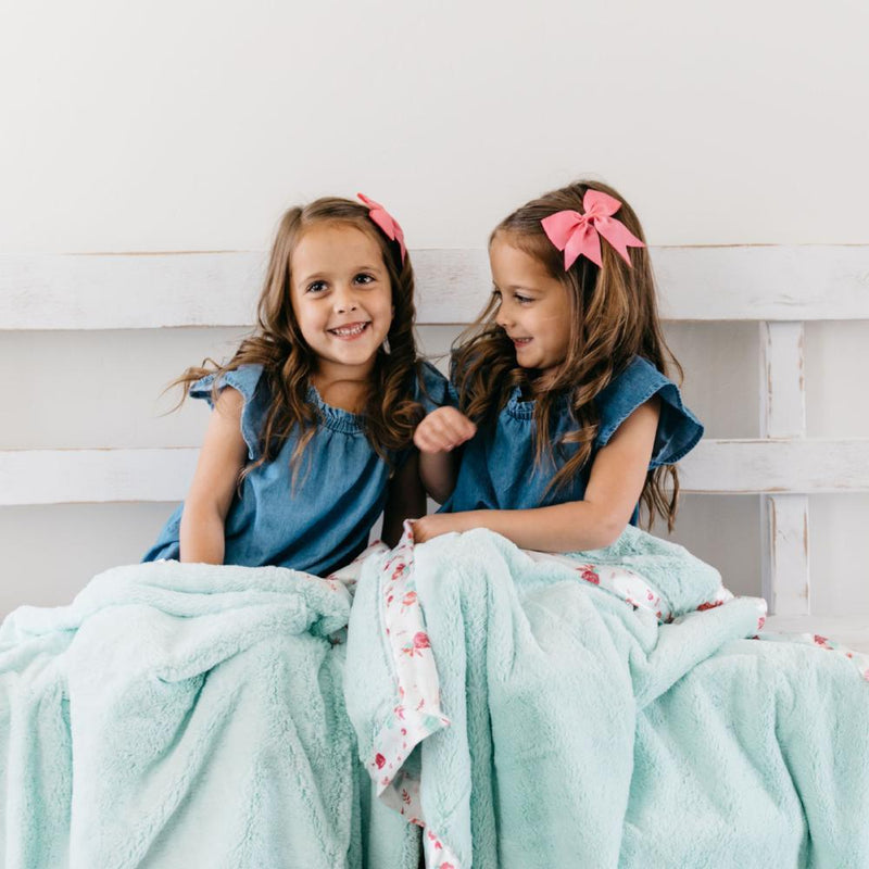 Two sisters sit on the bench with super soft mint mint colored blankets with satin on their laps.