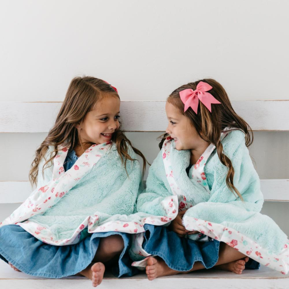 Two sisters sit with mint blankets with floral trim wrapped around their shoulders.