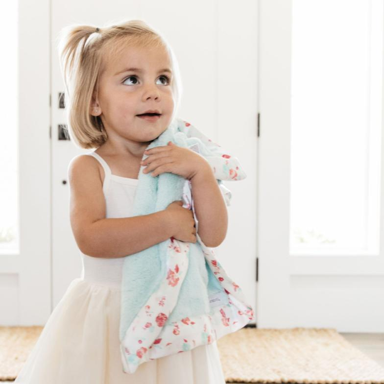 Toddler girl clasps her mint lovey with silky, floral satin border.