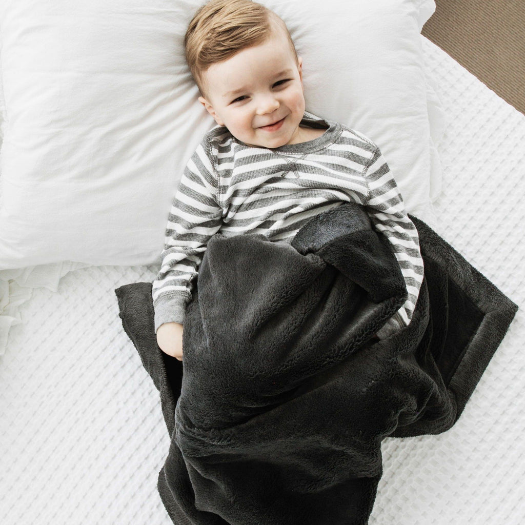 Young boy on white bed with dark gray baby blanket