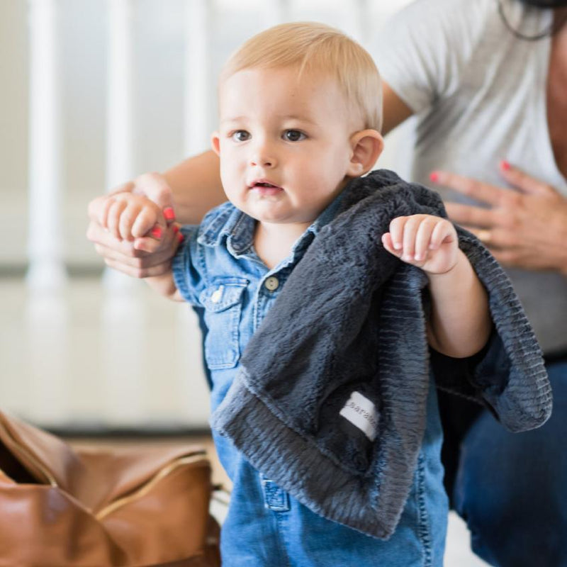 Baby boy walking with mini charcoal security blanket.