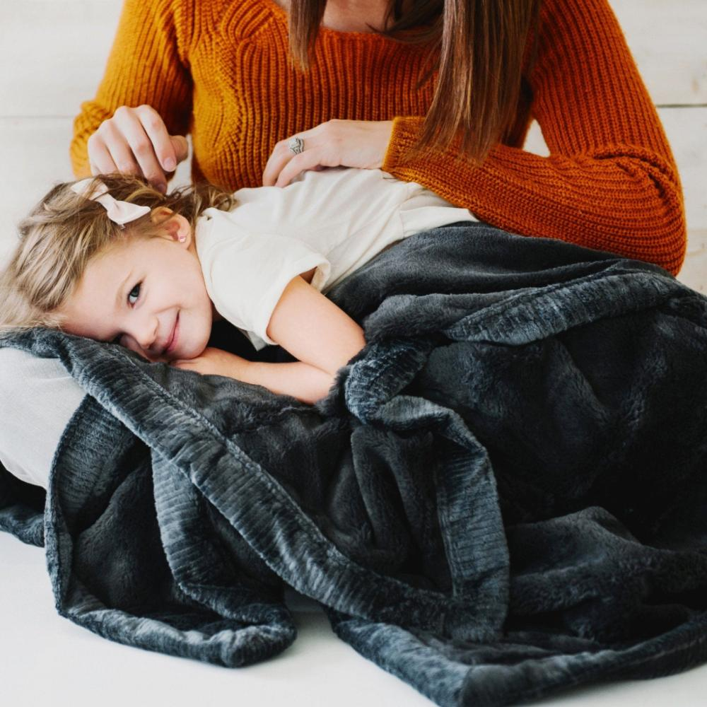 Little girl on her mom's lap cuddled in a black cozy blanket