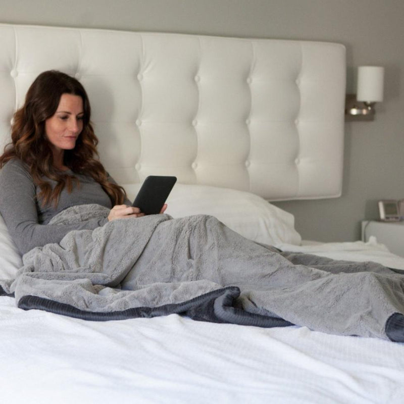 Brunette woman lounging in bed with a soft gray and charcoal Saranoni throw blanket.