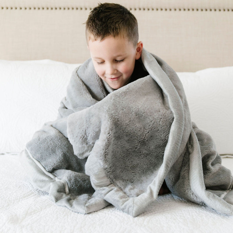 Little boy sitting on a bed wrapped in luxurious gray blanket for kids.