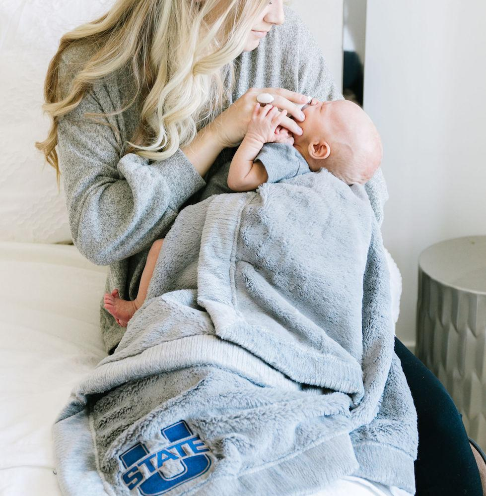 Alumni snuggles her baby in an extra large throw blanket with Utah State University logo embroidery.