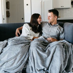 Cute couple snuggling under a large beautiful gray plush blanket on a couch.
