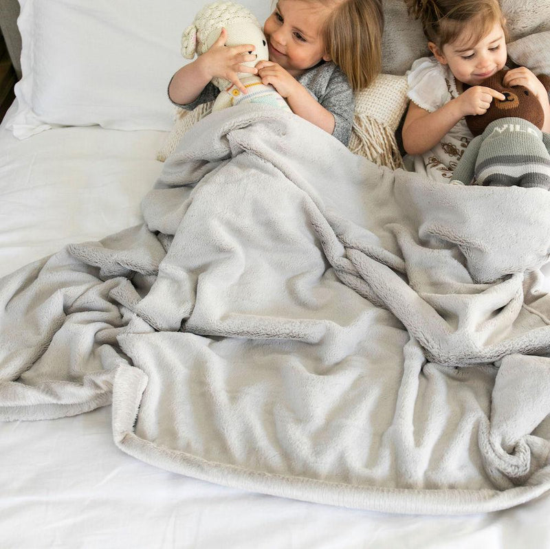 Young girls snuggling with their animals underneath a super soft neutral full size blanket.