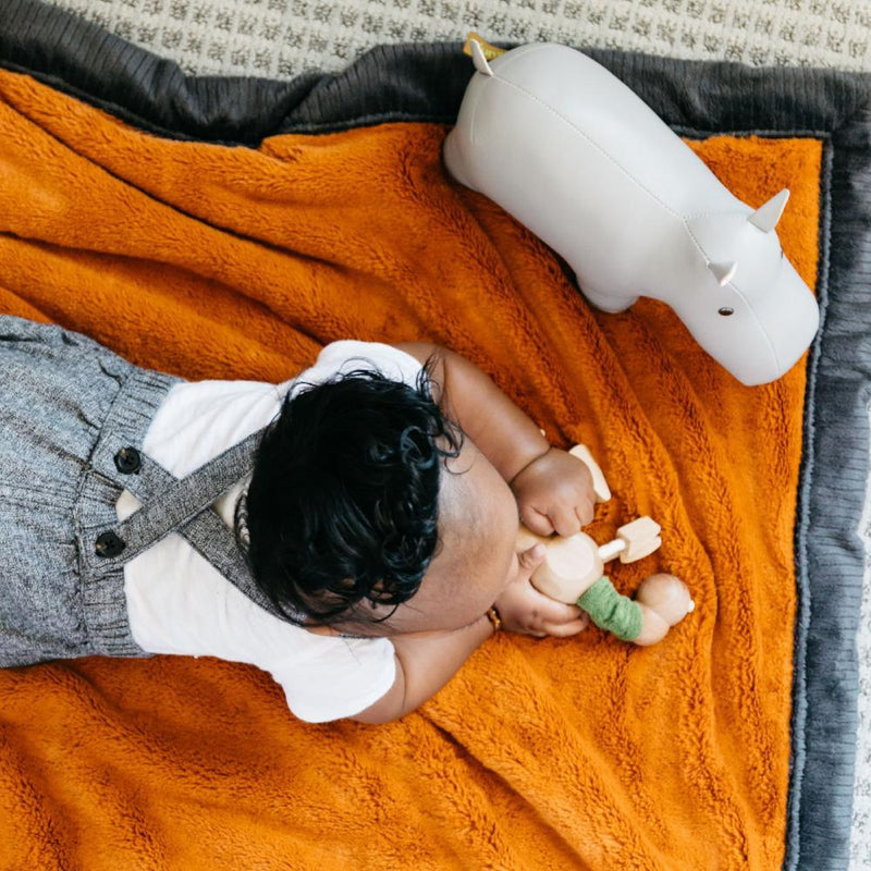 Toddler boy plays with his toys on top of a deep orange and charcoal lush blanket for kids.