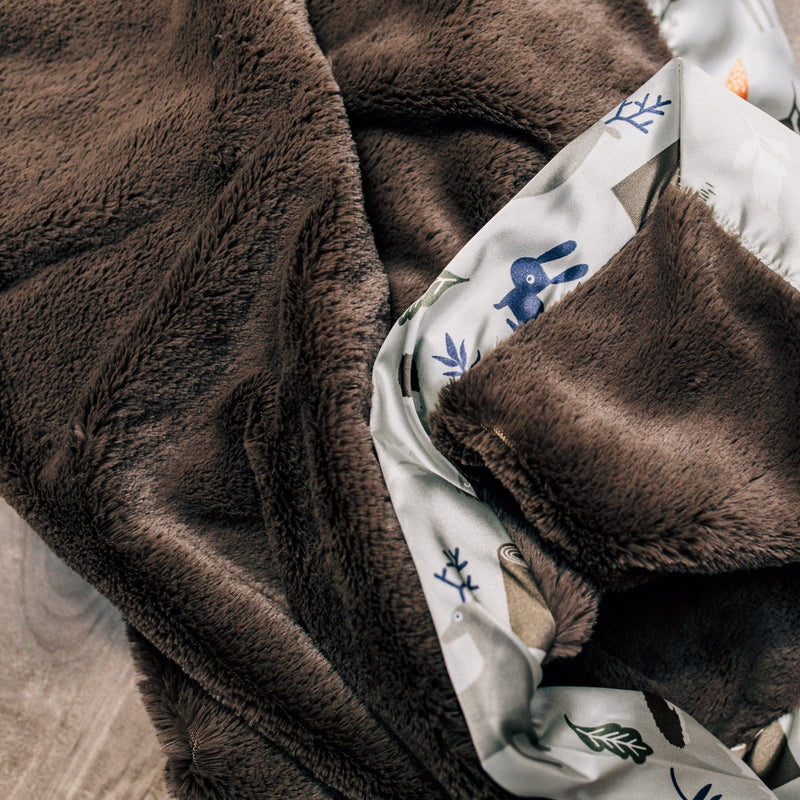 Brown blanket with animals on the satin trim.