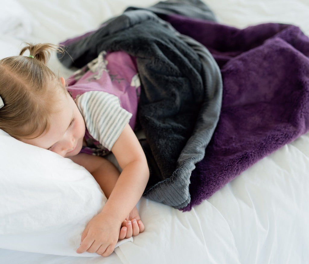 Young girl naps under her silky soft, deep purple girls throw blanket.