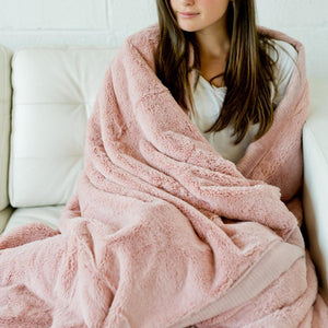 Teenage girl lounging on an elegant white chair while snuggled up in a beautiful blush extra large blanket.