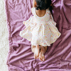 Little girl lays on her silky smooth, dusty purple lush throw for kids.