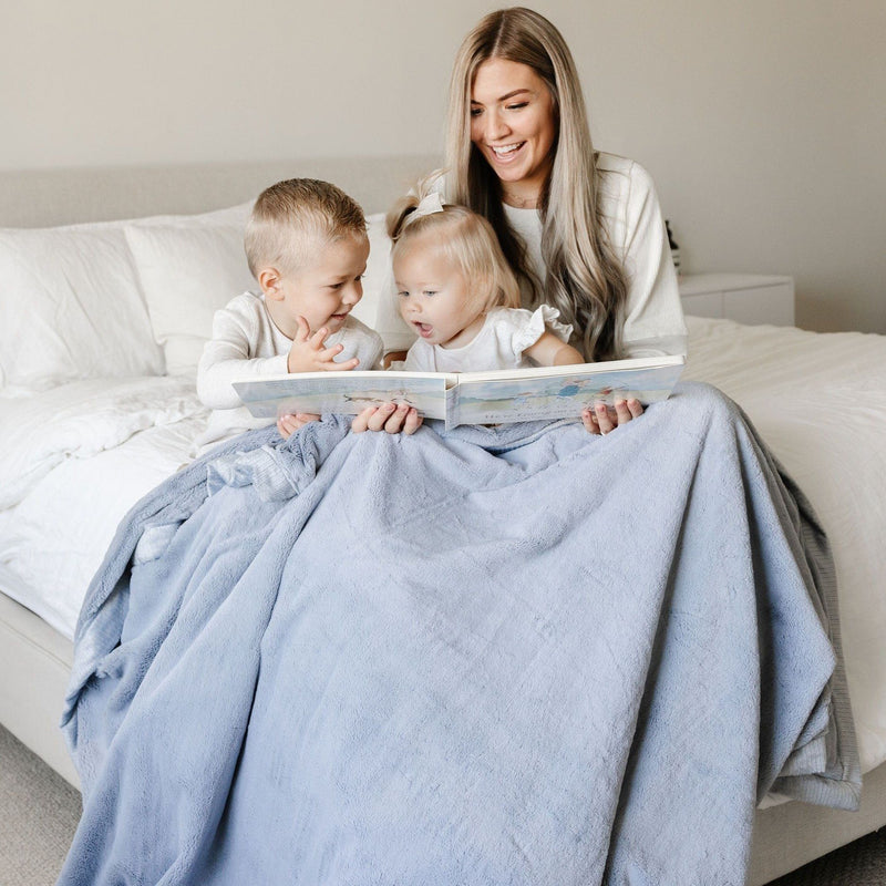 Beautiful blue and gray adult blanket being used as a comfy sitting blanket.