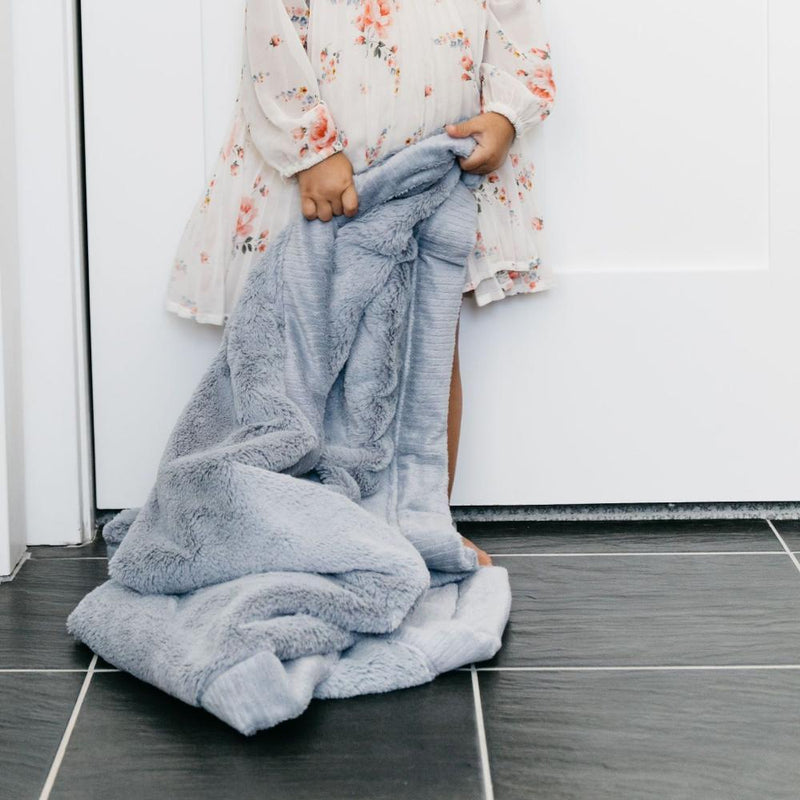 Little girl holding gray blue baby blanket