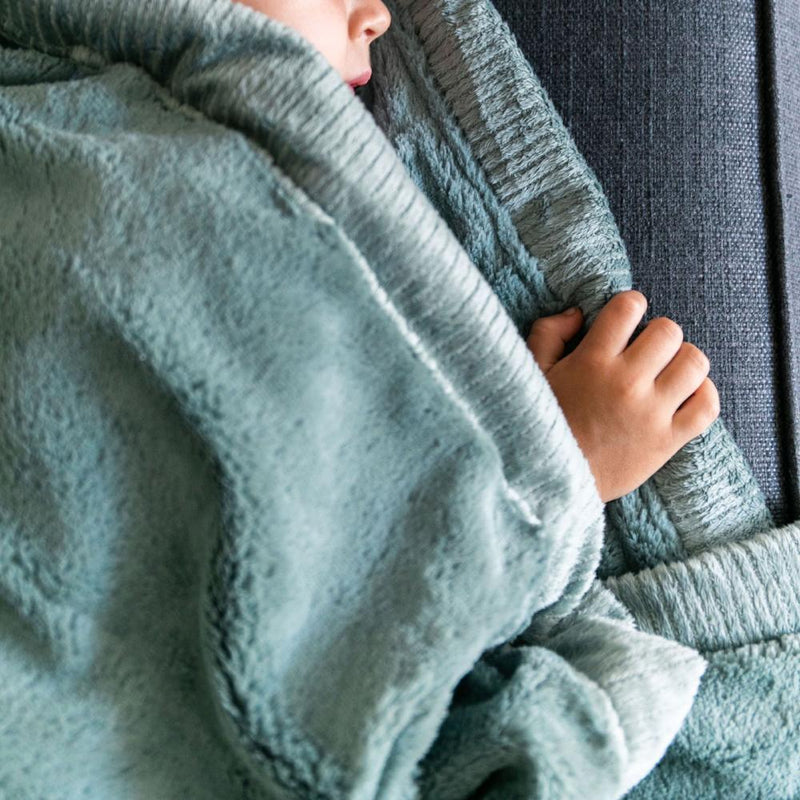 Toddler snuggles in his beautiful Saranoni lush eucalyptus toddler blanket.