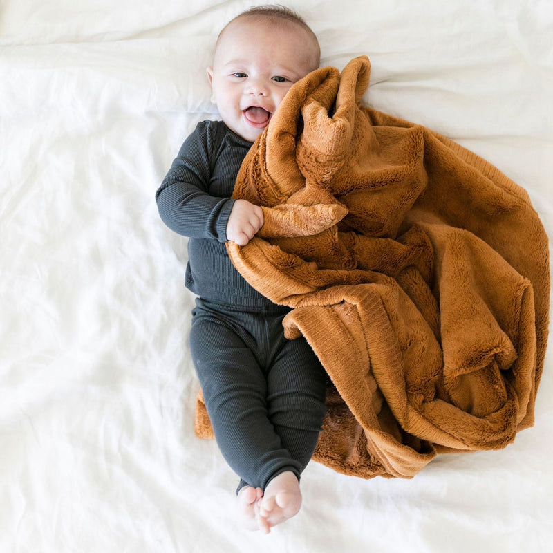 Baby in charcoal blanket snuggling rust colored soft blanket